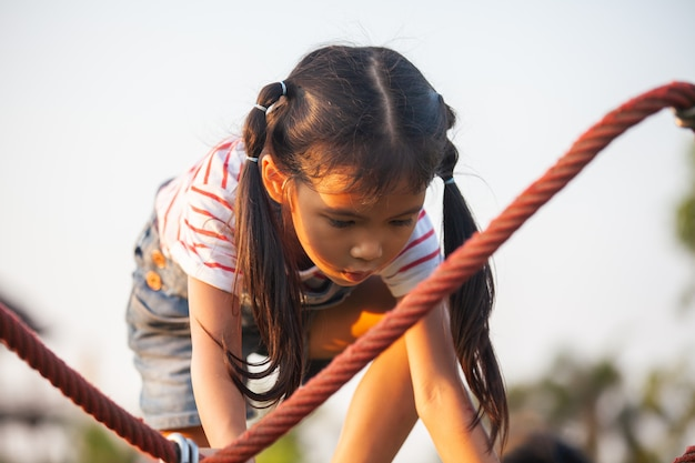 Das nette asiatische kindermädchen, das spaß hat, zu spielen und auf dem seil im spielplatz zu klettern