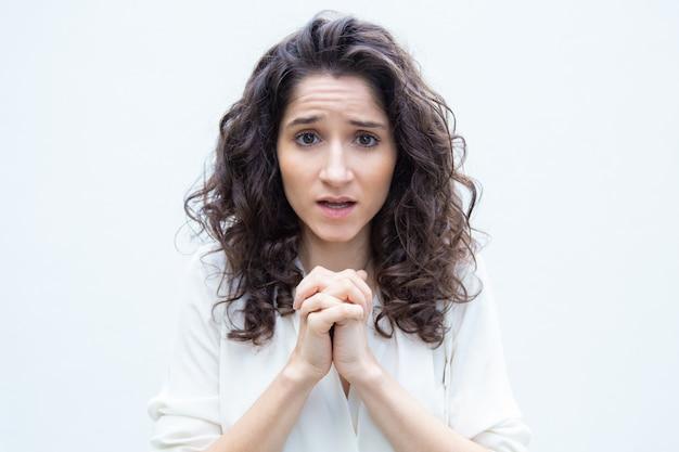 Das nette besorgte studentenmädchen, das hände in hält, beten geste