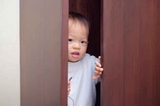 Das nette kleine asiatische kleinkind-babykind mit 18 monaten / 1-jährigem, das weiße strickjacke trägt, versteckt sich im wandschrank zu hause