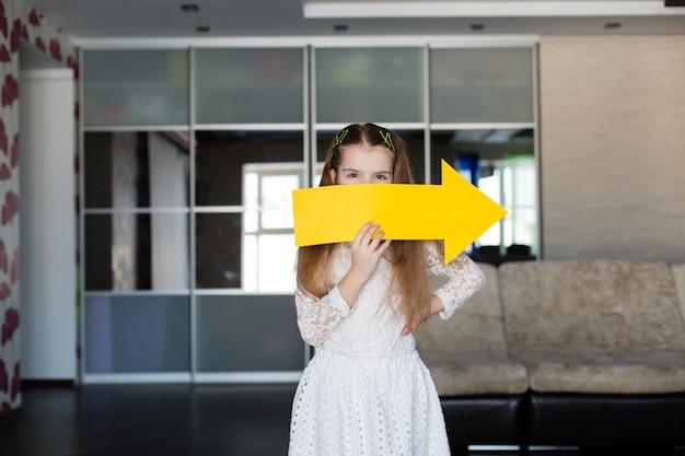 Das nette kleine mädchen, das ein leeres gelb hält, unterzeichnen in form eines pfeiles, der nach rechts zeigt