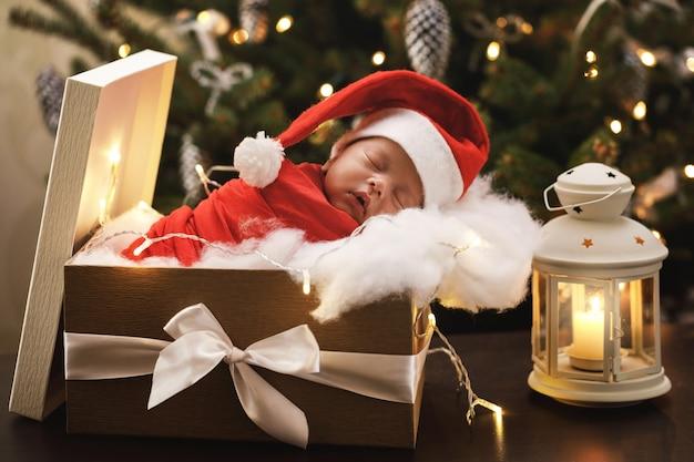 Das nette neugeborene baby, das santa claus-hut trägt, schläft in der weihnachtsgeschenkbox