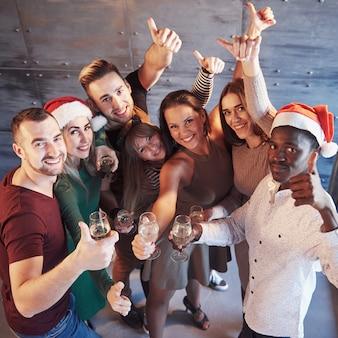 Das neue jahr kommt! gruppe nette junge multiethnische leute in sankt-hüten auf der partei, emotionales lebensstilleutekonzept aufwerfend