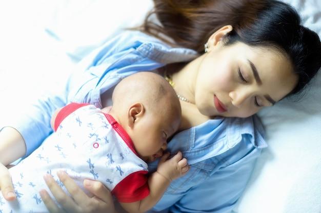 Das neugeborene baby, das auf der brust der mutter schläft