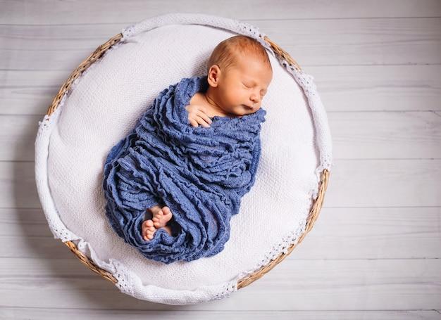 Das neugeborene baby, das im blauen schal eingehüllt wird, schläft auf weißem kissen