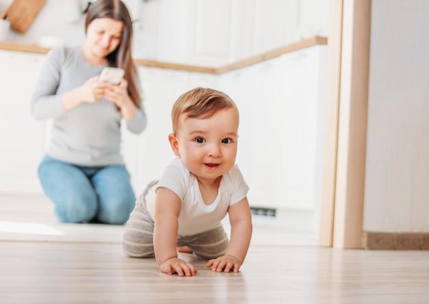 Das niedliche baby erforscht die welt, während mutter in ihrem smartphone in der küche surft