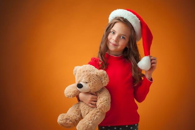 Das niedliche fröhliche kleine mädchen mit teddybär auf orange hintergrund