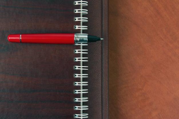Das notizbuch und ein roter stift liegen auf einem holzschreibtisch