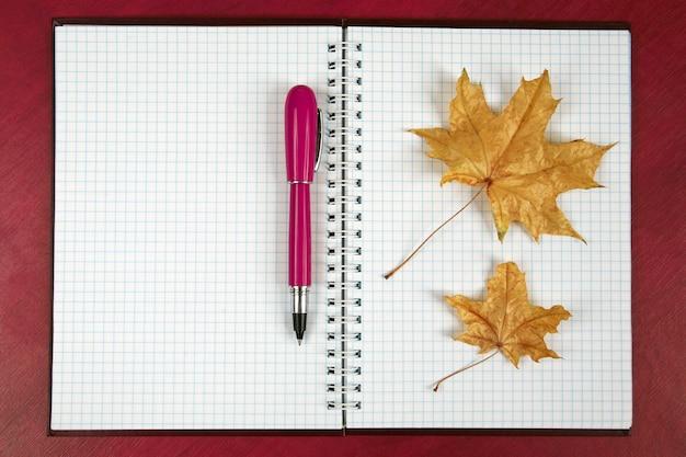 Das offene notizbuch und der rote stift mit dem herbstblatt, das auf einem holztisch liegt. themen für wirtschaft und bildung