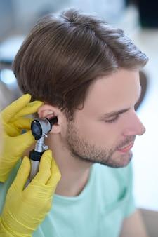Das ohr junger patienten wird mit einem auriskop untersucht