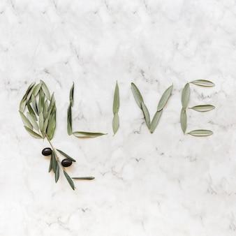 Das olivgrüne wort, das mit olive gemacht wird, verlässt auf marmorhintergrund