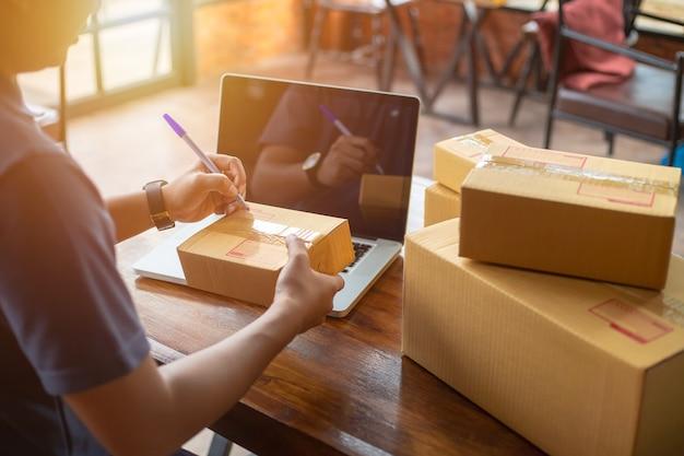 Das on-line-kaufende junge beginnen kleinunternehmen in einer pappschachtel bei der arbeit.