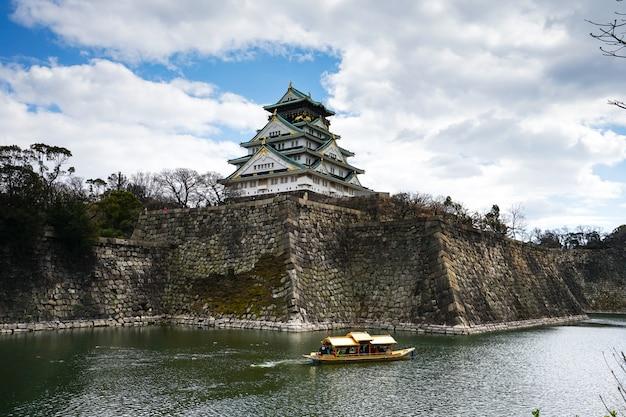 Das osaka-schloss in osaka, japan mit touristischer besichtigungsbootsfahrt um das osaka castleis