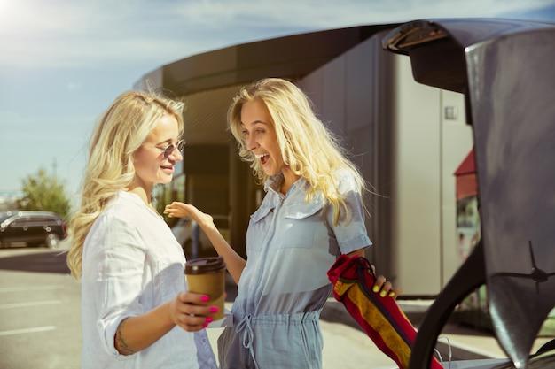 Das paar der jungen lesben bereitet sich auf urlaubsreise auf dem auto am sonnigen tag vor. einkaufen und kaffee trinken, bevor sie aufs meer oder meer gehen. konzept der beziehung, liebe, sommer, wochenende, flitterwochen.
