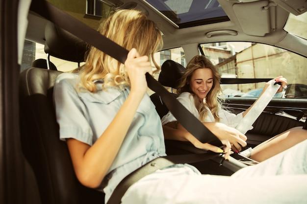 Das paar der jungen lesben bereitet sich auf urlaubsreise auf dem auto am sonnigen tag vor. frauen sitzen und bereit, zur see, zum fluss oder zum meer zu gehen. konzept der beziehung, liebe, sommer, wochenende, flitterwochen.