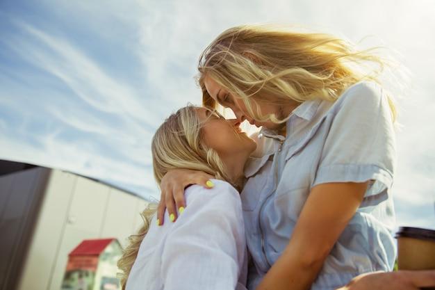 Das paar der jungen lesben bereitet sich auf urlaubsreise auf dem auto am sonnigen tag vor. kuscheln und kaffee trinken, bevor man aufs meer oder meer geht. konzept der beziehung, liebe, sommer, wochenende, flitterwochen.