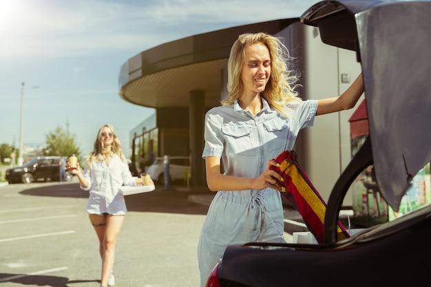 Das paar der jungen lesben bereitet sich auf urlaubsreise auf dem auto am sonnigen tag vor