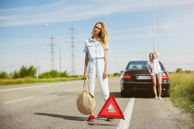 Das paar der jungen lesben, das an sonnigem tag auf dem auto urlaub macht