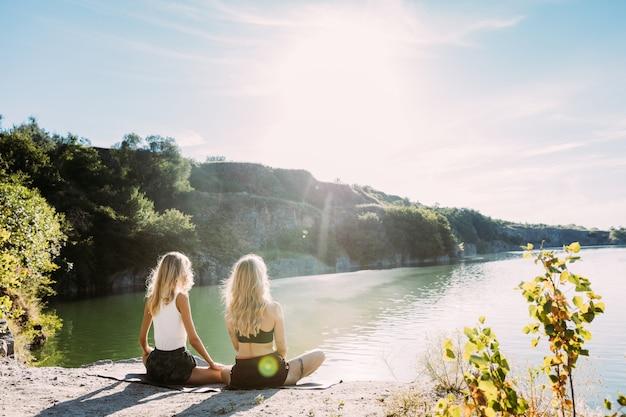 Das paar der jungen lesben, das spaß am flussufer im sonnigen tag hat