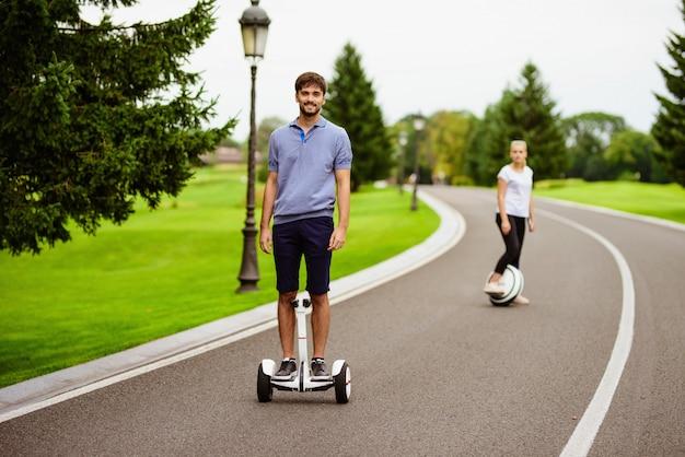 Das paar fährt im park ein gyroboard und ein monokel.