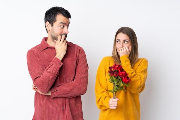 Das paar in valentine day, das blumen über lokalisierter wand hält, ist ein wenig nervös und erschrocken, hände zum mund setzend