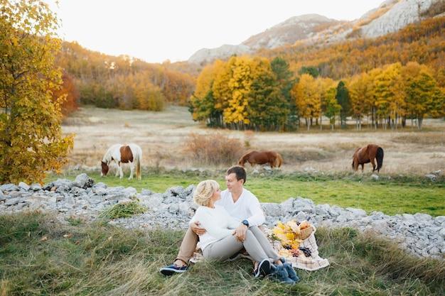 Das paar sitzt und umarmt sich auf einer decke gegen pferde, die im herbst grasen