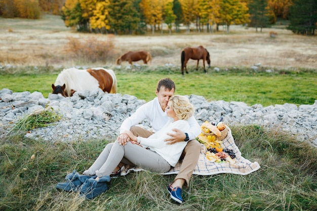 Das paar sitzt und umarmt sich auf einer decke mit essen auf dem rasen