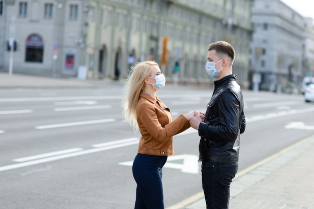 Das paar trägt eine medizinische maske, die während der verbreitung von nachrichten über die epidemie des coronavirus auf der straße der stadt läuft.