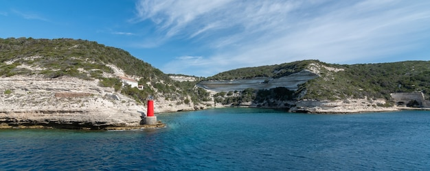 Das panorama der yacht zum leuchtturm rockt den blauen himmel mit der horizontalen ausrichtung der kleinen wolken