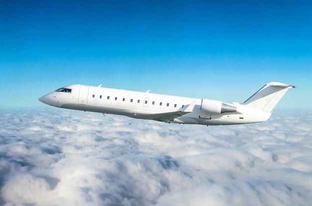 Das passagierflugzeug fliegt auf flughöhe durch lauten und blauen himmel