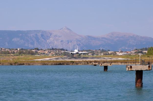 Das passagierflugzeug landet am flughafen kerkyra. griechenland, korfu insel. abnahme der höhe. landebahn auf dem hintergrund der berge und des meeres.