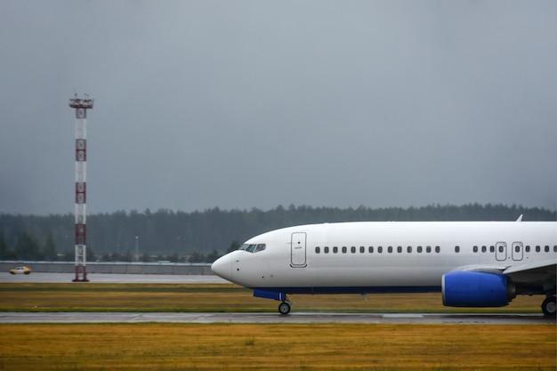 Das passagierflugzeug landete bei schlechtem wetter mit regen auf der landebahn des flughafens