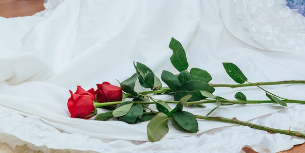 Das perfekte hochzeitskleid mit einem vollen rock im zimmerhochzeitskleid hält rote rose