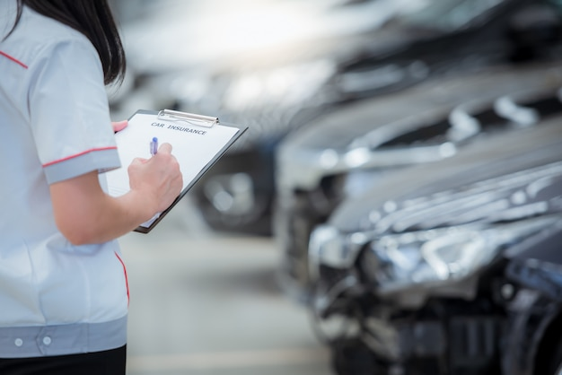 Das personal des versicherungsagenten schreibt während der überprüfung des fahrzeugs in die zwischenablage, nachdem es bewertet wurde und den unfall geltend gemacht hat - das auto ist unfallversichert.