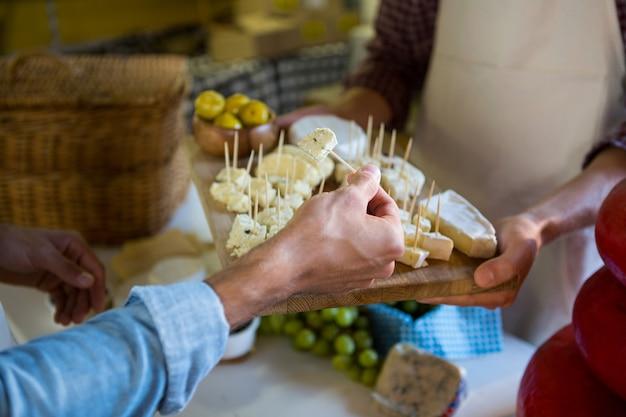 Das personal zeigt dem kunden am schalter eine käseprobe
