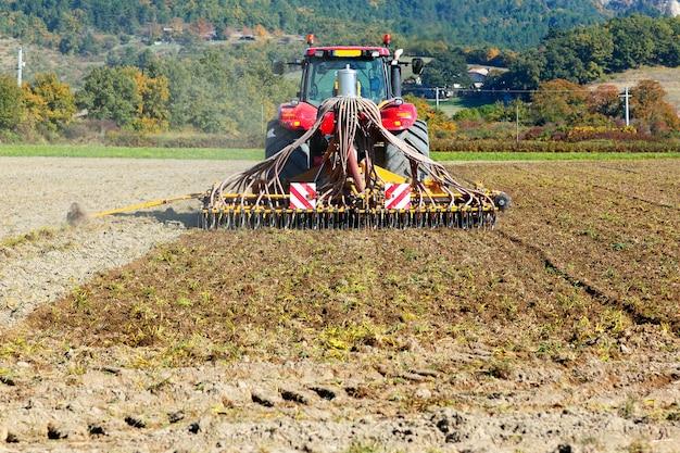 Das pflügen eines schweren traktors während des anbaus arbeitet auf dem feld mit dem pflug