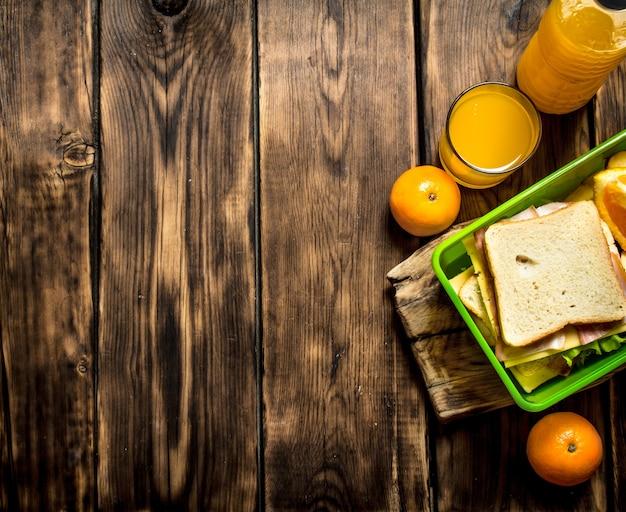 Das picknick-set sandwiches mit käse und speck, obst und orangensaft