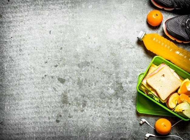 Das picknick stellte sandwiches, orangensaft und obst auf den steintisch