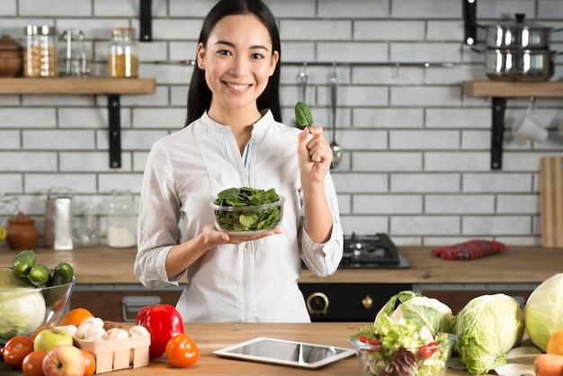 Das porträt der asiatischen frau grünen basilikum zeigend, verlässt in der küche