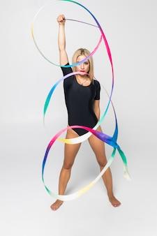Das porträt der calilisthenics-übung der turnerin der jungen frau, die mit band trainiert. kunstgymnastikkonzept.