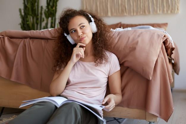 Das porträt der denkenden jungen lockigen mulattendame, die im zimmer sitzt, sein lieblingslied genießt und eine neue zeitschrift über kunst liest, schaut nachdenklich weg.