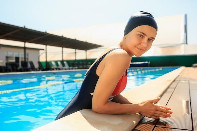 Das porträt der glücklichen lächelnden schönen frau am schwimmbad.