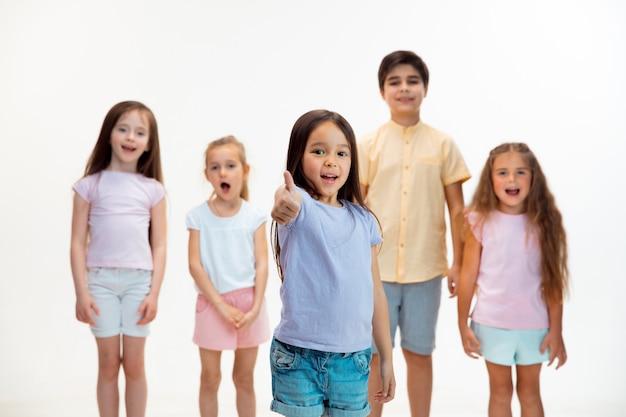Das porträt der glücklichen niedlichen kleinen kinderjungen und -mädchen in der stilvollen freizeitkleidung, die vorne gegen weiße studiowand schaut