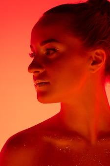 Das porträt der hübschen frau lokalisiert auf rot-orangeem studiohintergrund im neonlicht, monochrom. schönes weibliches modell. konzept menschlicher emotionen, gesichtsausdruck, verkauf, werbung, mode und schönheit.