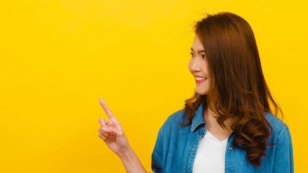 Das porträt der jungen asiatischen dame, die mit mit fröhlichem ausdruck lächelt, zeigt etwas erstaunliches an der leeren stelle in der freizeitkleidung und betrachtet kamera über gelber wand. gesichtsausdruck konzept.