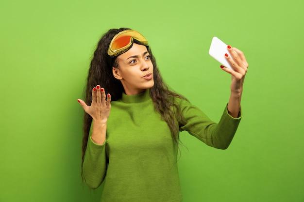 Das porträt der jungen brünettenfrau der afroamerikaner in der skimaske auf grün