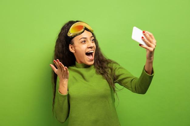 Das porträt der jungen brünettenfrau der afroamerikaner in der skimaske auf grünem studiohintergrund. konzept der menschlichen emotionen, gesichtsausdruck, verkauf, anzeige, wintersport und feiertage. selfie oder vlog machen.
