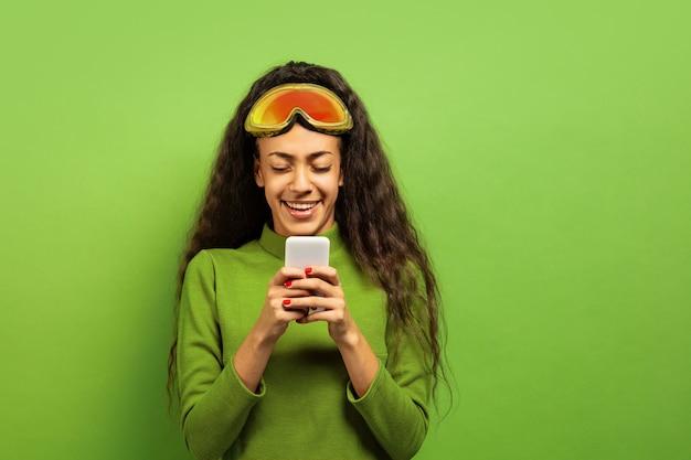 Das porträt der jungen brünettenfrau der afroamerikaner in der skimaske auf grünem studiohintergrund. konzept der menschlichen emotionen, gesichtsausdruck, verkauf, anzeige, wintersport und feiertage. smartphone benutzen.