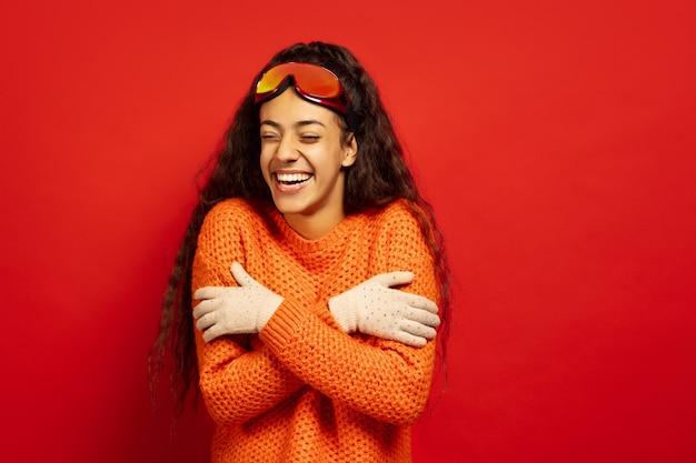 Das porträt der jungen brünettenfrau der afroamerikaner in der skimaske auf rotem studiohintergrund. konzept der menschlichen emotionen, gesichtsausdruck, verkauf, anzeige, wintersport und feiertage. erwärmen in kälte, lachen.