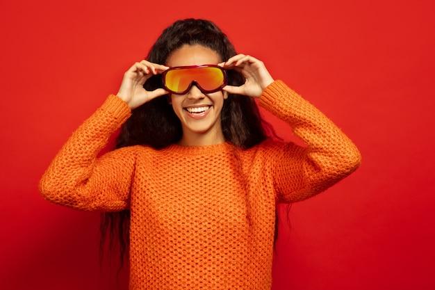 Das porträt der jungen brünettenfrau der afroamerikaner in der skimaske auf rotem studiohintergrund. konzept der menschlichen emotionen, gesichtsausdruck, verkauf, anzeige, wintersport und feiertage. lächelnd, brille tragend.