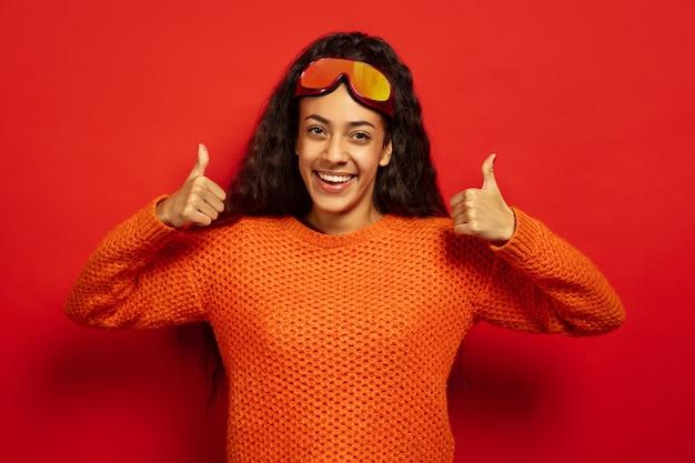 Das porträt der jungen brünettenfrau der afroamerikaner in der skimaske auf rotem studiohintergrund. konzept der menschlichen emotionen, gesichtsausdruck, verkauf, anzeige, wintersport und feiertage. lächelt und daumen hoch.